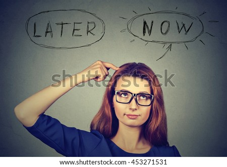 Now or later. Woman thinking looking up isolated on grey wall background. Human face expression. Time to act