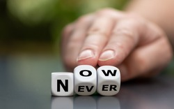 Now or never? Hand turns dice and changes the word