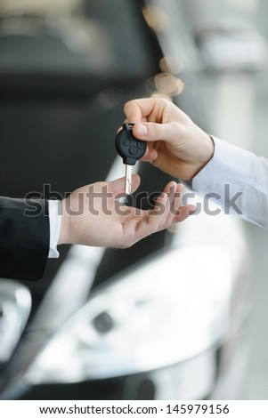 Now this car is yours. Car salesman giving the key to the new car owner