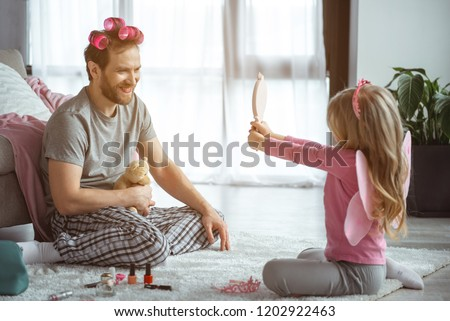 Now you are beautiful. Excited daughter is showing mirror to her father after playing. Man has makeup and curlers on hair. He is sitting on floor and laughing