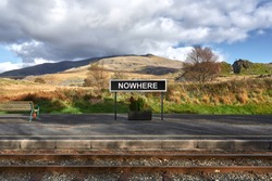 Nowhere descriptive station sign board on platform of remote railway station in rural mountain setting.