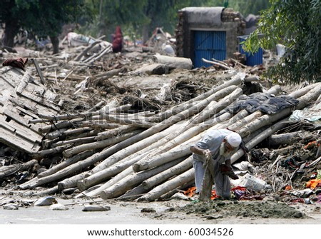 NOWSHERA, PAKISTAN - AUG 29: A man picks through debris of his house on August 29, 2010 in Nowshera. The house was destroyed by flood waters.