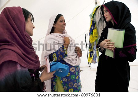 NOWSHERA, PAKISTAN - SEPT 7: UNHCR Goodwill Ambassador, Angelina Jolie  talks with flood affected women during her visits at Kandaro II Camp in Nowshera, Pakistan on Sept 07, 2010 - stock photo