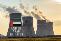 Nuclear plant chimneys displaying flag of United Arab Emirates with according text. Energy pollution accidents in the UAE concept. Power production and generation from atomic energy.