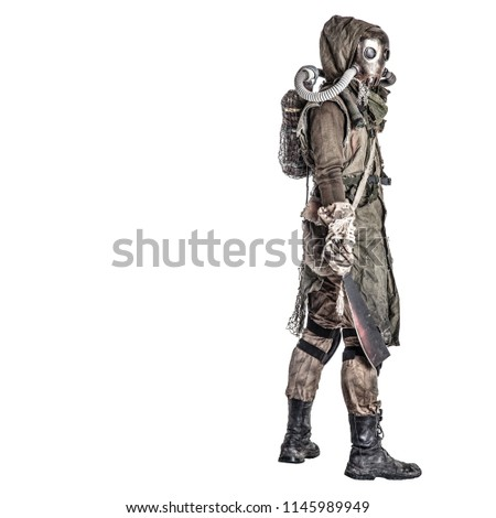 Nuclear post-apocalypse survivor creature in dirty tattered rags and creepy face gas mask, armed with handmade machete, standing sideways and looking over shoulder isolated on white studio shoot