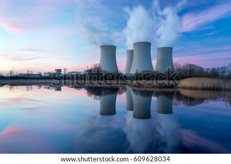 Nuclear power plant after sunset. Dusk landscape with big chimneys.