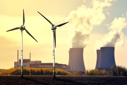 Nuclear power plant and wind turbines at sunset - Green energy concept