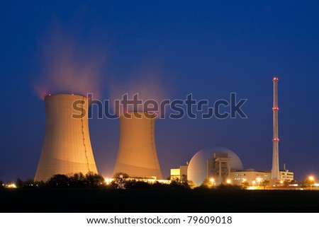 Nuclear power plant at night in Grohnde near Hameln  in Lower Saxony, Germany.  At the left are the cooling towers with water vapor, at the right the reactor.
