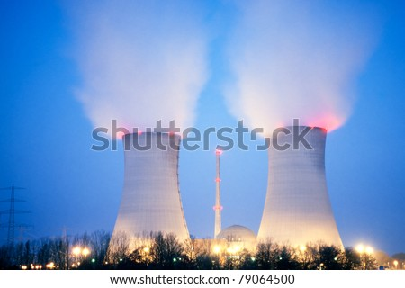 Nuclear power plant blowing huge clouds into dusky sky.
