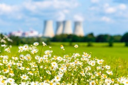 Nuclear power plant out of focus on the background of beautiful green and blooming summer meadow. Temelin, Czech Republic.