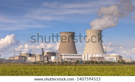 Nuclear power plant with steaming cooling towers under blue summer sky in Belgium