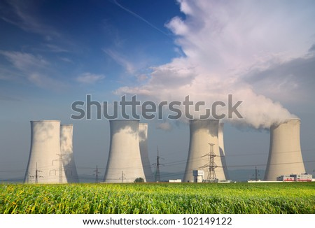 Nuclear power plant with summer field and big blue clouds.