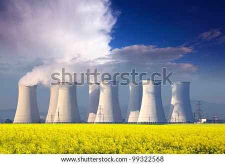 Nuclear power plant with yellow field and big blue clouds.