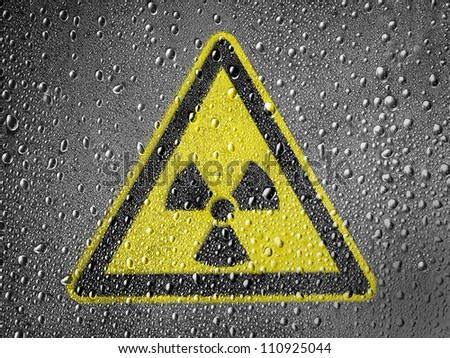 Nuclear radiation sign drawn on metal surface covered with rain drops