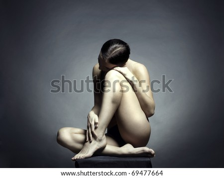 Nude beautiful sitting lady on black background
