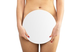 Nude beautiful woman holding a round sign in her hands and covering them with genitals on a white background isolate. Lower body