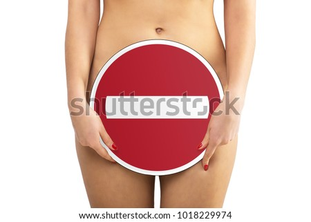 Nude beautiful woman holding a round sign in the hands of a sign-out sign banned and covering them with genitals on a white isolate background. Sex is forbidden. Lower part of the body. #1018229974