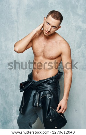 Nude elegant handsome man with a jacket on a belt with a short haircut on a gray background