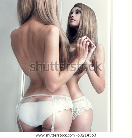 Nude girl in beautiful underwear in front of the mirror - stock photo