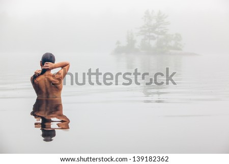 Nude middle aged Caucasian woman bathing and washing hair in Maine lake on a foggy Summer morning.