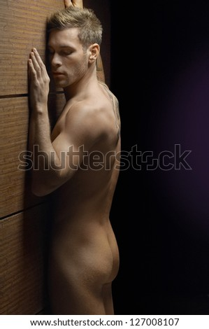 Nude muscular man with eyes closed standing isolated over studio background