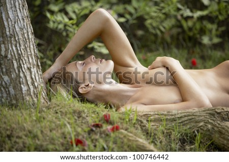 Nude young woman laying down on green grass and red rose petals, with tree roots in the foreground.