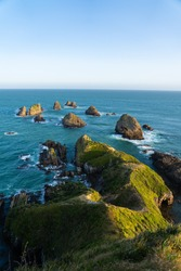 Nugget Point Lighthouse in New Zealand, famous landmark. Vertical composition