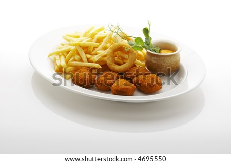 Nuggets, french fries and fried onion rings on the plate