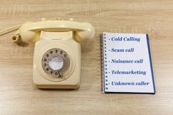 Nuisance telephone calls concept - old fashioned telephoned with notepad