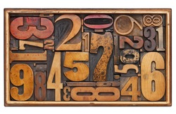 number abstract - random vintage wood letterpress prinitng blocks in a wooden box isolated on white