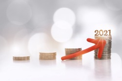Number 2021 and stack of coins with red arrow upwards on abstract background. Saving with return on investment concept and new year sustainable economic growth idea