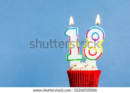 Number 18 Birthday Candle In A Cupcake Against Blue Background 1026050086