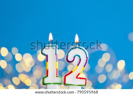 Number 12 Birthday Celebration Candle Against A Bright Lights And Blue Background 790595968