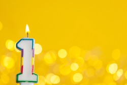 Number 1 birthday celebration candle against a bright lights and yellow background