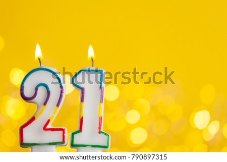 Number 21 Birthday Celebration Candle Against A Bright Lights And Yellow Background 790897315