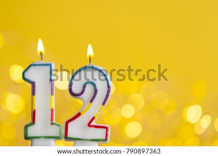 Number 12 Birthday Celebration Candle Against A Bright Lights And Yellow Background 790897363