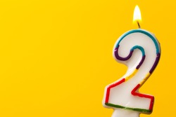 Number 2 birthday celebration candle against a bright yellow background