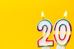 Number 20 birthday celebration candle against a bright yellow background