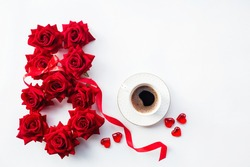 Number eight made from beautiful scarlet roses and a coffee mug isolated on white background. Greeting card for Women's Day on March 8. Copy space for text. March 8 and the concept of