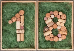 Number 18 eighteen made of wine corks on green background in wooden box