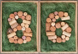 Number 86  eighty six  made of wine corks on green background in wooden box