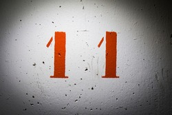 number eleven painted red on white irregular cement wall
