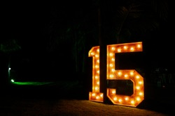 Number fifteen with lights on and clear - fifteen years - fifteen illuminated - large and clear number against dark background