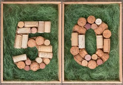 Number 50 fifty  made of wine corks on green background in wooden box