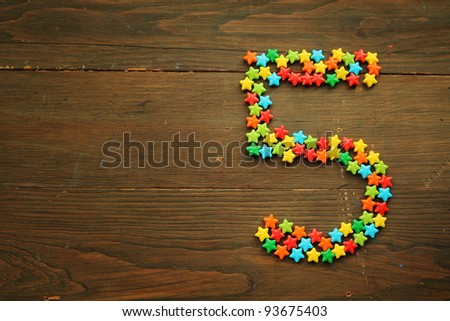 Number five made with star shape candies on a wooden table