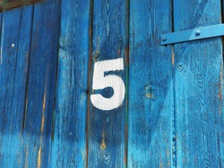 Number five on an old abandoned blue colour wooden gate in Budapest suburb, Hungary