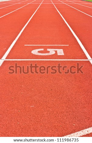 Number five on the start of a running track
