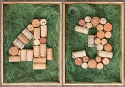 Number 43 forty three  made of wine corks on green background in wooden box