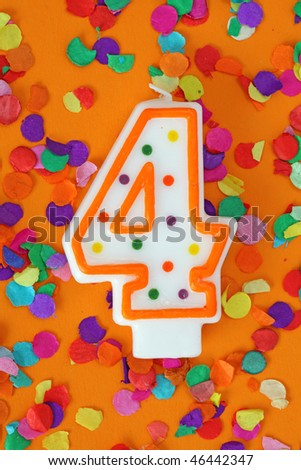 Number four birthday candle on orange background