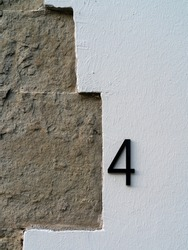 number four on a stone wall for the indication of house number